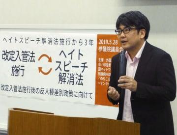集会で差別の現状を報告する安田浩一氏=29日午後、国会