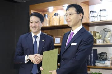 Yutaro Yotsuzuka (R), managing director of Mitsubishi Estate Asia Pte. Ltd., and Raimon Land Public Co. CEO Lionel Lee shake hands at a press event in Bangkok on May 28, 2019, for the One City Centre office development project in the Thai capital. (N