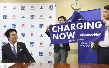 寝具メーカーの西川が配布するタオルケットを披露し、パワーナップを推奨する福岡市の高島宗一郎市長(左)=29日、福岡市役所