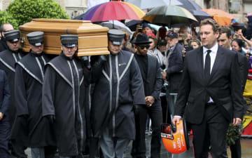 ニキ・ラウダ氏のひつぎの前で、ラウダ氏のヘルメットを持って歩く息子(右)ら=29日、ウィーン(AP=共同)