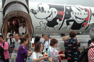 ファンら約200人が特別塗装機に搭乗し、ミッキーマウスのスクリーンデビュー90周年を祝った=29日、成田空港