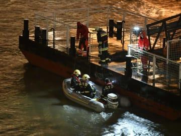 ハンガリー首都ブダペストのドナウ川で、犠牲者の捜索に向かう準備をする救助隊員=29日(AP=共同)