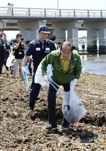 「海ごみゼロウィーク」の開幕イベントで、海岸のごみを拾う原田環境相(手前)=30日午前、神奈川県藤沢市