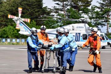 訓練で、ヘリコプターから降ろした要救助者を運ぶ機動救難士ら