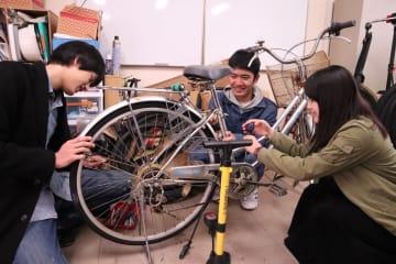 作業場で工具などを使って自転車を整備するメンバー=長崎大文教キャンパス