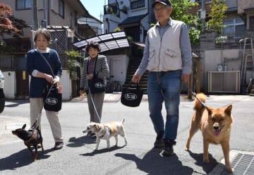 結成10周年記念で作成した手提げバッグを手に愛犬と散歩する隊員(京都府長岡京市奥海印寺)