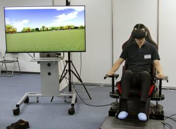 NTTコミュニケーション科学基礎研究所が公開した、座っているのに歩行しているかのような感覚を得られる技術の実演=30日、京都府精華町