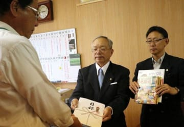 目録を手渡す大森会長(中央)