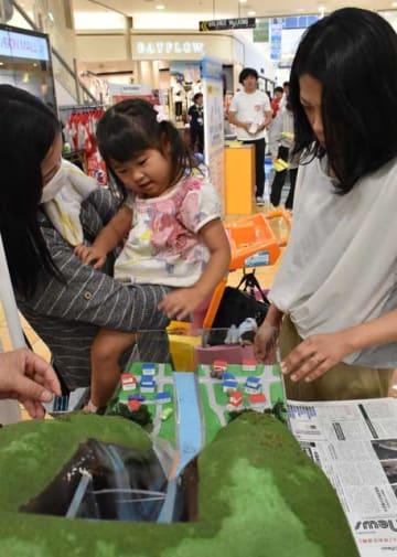 土石流を再現する模型を見て災害の危険性を確認する家族連れ