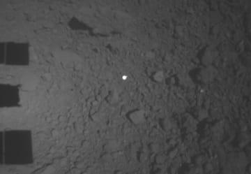 はやぶさ2が放出した目印のボール(中央の白い丸)。画面左ははやぶさ2の機体の影(JAXA、千葉工大提供)