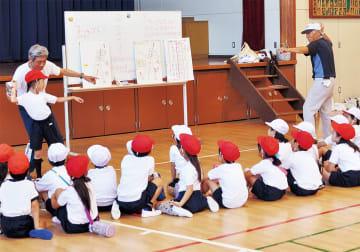 子どもたちに「じゃん・けん・ぽん」の掛け声でボールを投げるよう手取り足取り教える川村さん(左)