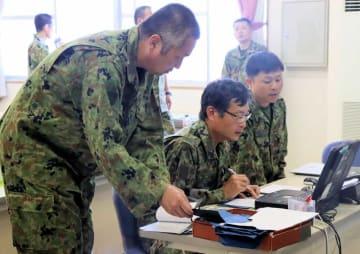 自衛隊員(左)から情報処理の訓練を受ける府職員=福知山市天田・陸上自衛隊福知山駐屯地