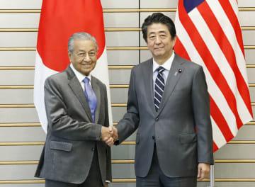 会談前に握手するマレーシアのマハティール首相(左)と安倍首相=31日午前、首相官邸