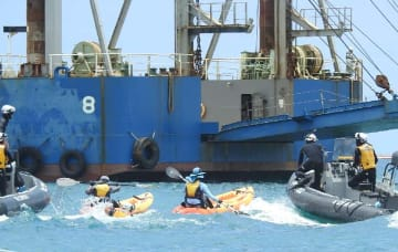 埋め立て土砂を積んだ作業船の接岸を阻止しようとカヌーでフロートを乗り越え抗議する市民=31日、名護市辺野古