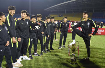 「パンダカップ」の優勝トロフィーを踏み、ポーズをとる韓国チームの選手=29日、中国四川省成都市(共同)