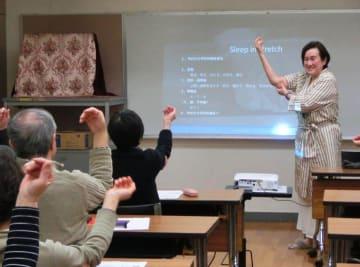 「睡眠セミナー」で参加者に独自の体操を指導するヨシダさん(右)=2019年2月、本牧地区センター