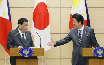 共同記者発表を終え、フィリピンのドゥテルテ大統領(左)に握手を求める安倍首相=31日午後、首相官邸
