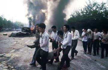 劉建さんが1989年4月16日ごろから、武力弾圧が起きた6月4日までの約50日間に北京で撮影した写真。当局との衝突で負傷したとみられる人を運ぶ男性らの姿がとらえられていた(共同)