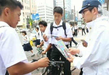 自転車に乗った高校生にチラシを渡し、安全利用を呼び掛ける警察官=31日、大分市府内町
