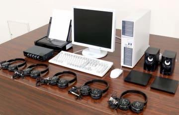 通信傍受に使われるパソコン型の「特定電子計算機」やヘッドホン(手前)、プリンター(左奥)、記録媒体(右中)など=福井県警本部