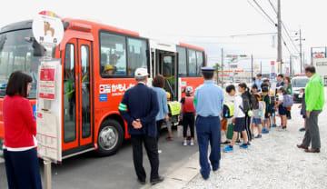 【バスで登校する児童らを見守る西署員や防犯ボランティアら=菰野町神森のバス停で】
