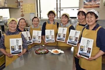 完成した「まなかのカフェのレシピ本」を手にし、10年目の営業開始へ意気上がる町特産品販売促進協議会のメンバー