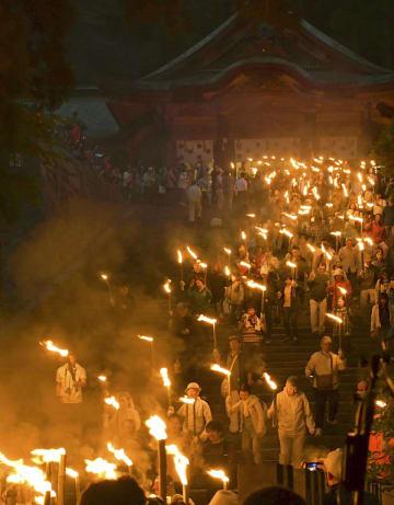 大山の夏山開きの前夜祭で、たいまつを手に歩く人たち=1日夜、鳥取県大山町