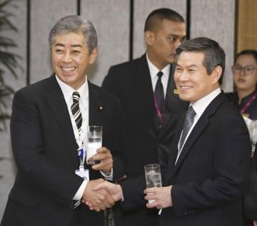 「アジア安全保障会議」の昼食会会場で韓国の鄭景斗国防相(右)と握手する岩屋防衛相=1日、シンガポール(共同)