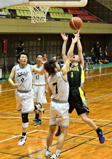 【バスケットボール】ディフェンスをかわしながらゴールを狙う選手=宮崎市・県体育館
