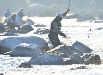 解禁日にアユを釣り上げる釣り人=1日午前6時半、大子町下野宮、鹿嶋栄寿撮影