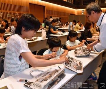 新聞でバッグを作る参加者=太田市民会館
