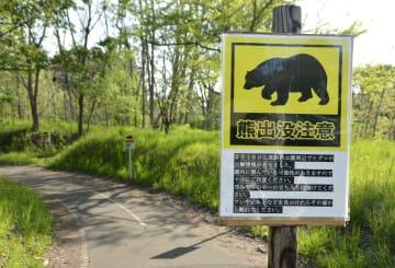 真駒内公園に設置された、目撃情報などが記載された「熊出没注意」の看板=5月17日、札幌市南区