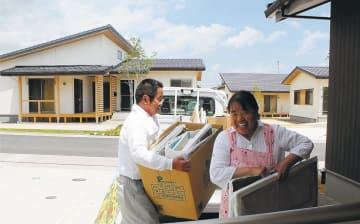 避難先から運んできた荷物を災害公営住宅に運び入れる夫婦=1日、福島県大熊町