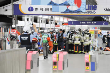 事故車両(左)が止まったホームに集まる警察官や消防隊員ら=1日午後9時15分ごろ、横浜市磯子区のシーサイドライン新杉田駅