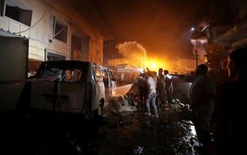 2日、シリア北部アザーズで、車爆弾の爆発現場で消火に当たる人々(ロイター=共同)
