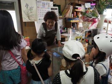 開店50年を迎え、にぎわう子どもたちの対応をする水越たみさん(中央奥)=2日、君津市坂田の「やつ商店」