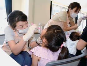 歯科医から歯磨き指導を受ける子ども