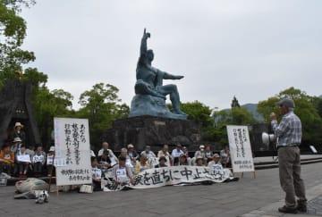 米国の臨界前核実験に抗議して座り込みをする被爆者ら=長崎市、平和公園