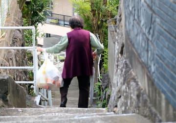 ごみステーションに向かうため階段道を下る高齢女性=長崎市内