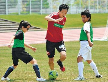 プロ選手と一緒にサッカーを楽しむ子どもたち