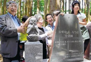 記念碑を囲み、思い出を語る勝吉さん(左端)、ゆう子さん(左から3人目)、甲七さん(左から4人目)