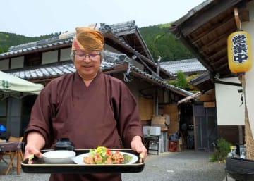 「美・火水」で唐揚げ定食を紹介する秋山さん(京都府南丹市八木町神吉)