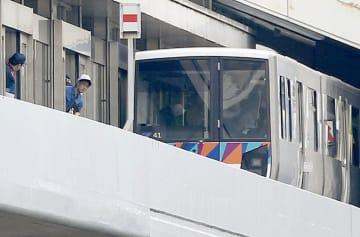 「金沢シーサイドライン」の新杉田駅で車両と現場を調べる関係者=2日午後
