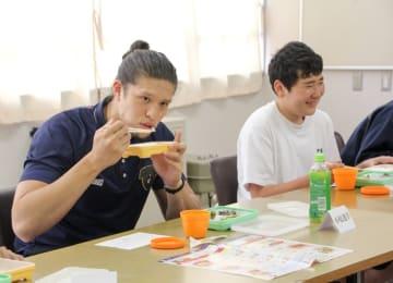 生徒と会話を楽しみながらハマ弁を試食する小原選手(左)=横浜市立上飯田中学校