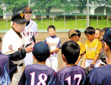 子どもたちを指導する元巨人の黒江透修さん(左)。左奥は広野功さん=羽生市東の羽生中央公園野球場
