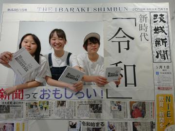 ライブの合間に新聞型パネルで記念撮影を楽しむ「みならいモンスター」のメンバー=つくば市小野崎