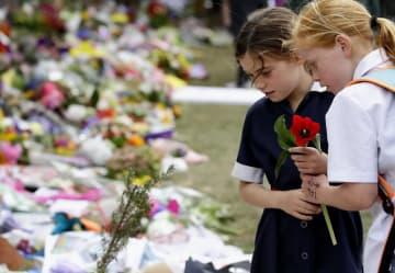 ニュージーランド・クライストチャーチの銃乱射事件で、市が設けた追悼場所に花を手向ける少女=21日(共同)