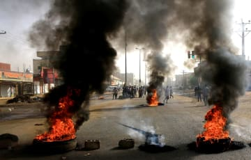スーダンの首都ハルツームで、民主化を求める人々が作った、炎上するタイヤのバリケード=3日(ロイター=共同)