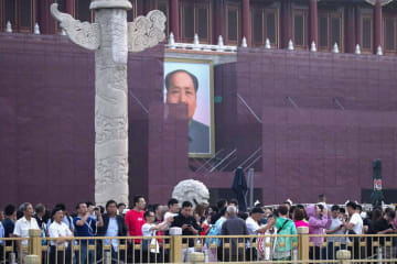 隣接する天安門広場の国旗掲揚を見るため、天安門前に集まった人たち=4日、北京(AP=共同)