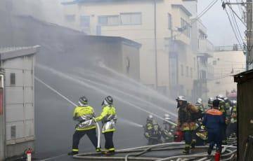 煙を上げる工場に放水する消防士=4日午後3時40分ごろ、相模原市中央区